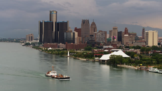 barge passing downtown detroit with ambassador bridge in the background - aerial - barge stock videos & royalty-free footage