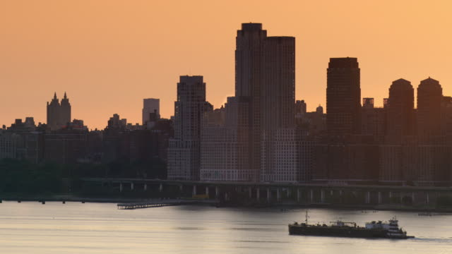 Barge slowly moves up the Hudson River along the West Side skyline in New York City.