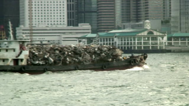 ms zo ws barge transporting trash in front of skyline, hong kong, china - barge stock videos & royalty-free footage
