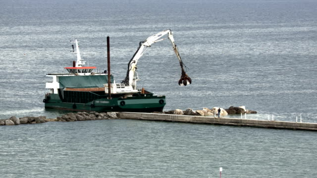 barge with crane positions reefs to protect the beach - barge stock videos & royalty-free footage