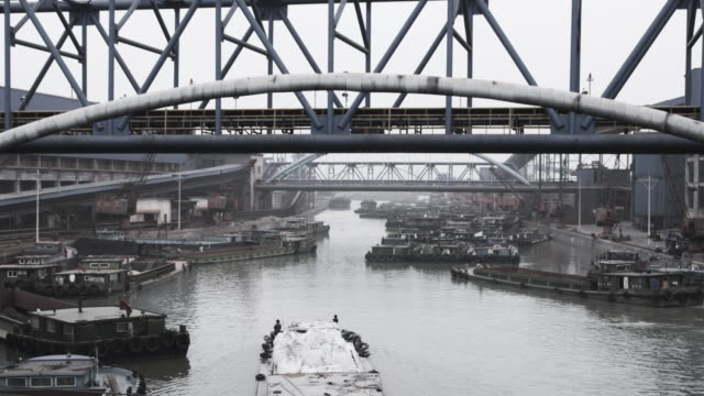 Barges float in a busy polluted canal under a metal train bridge.