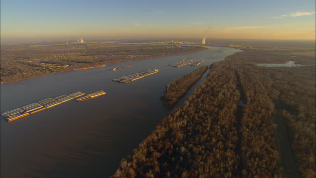 aerial ws barges traveling on mississippi river with smoke stacks in distance / laplace, louisiana, usa - louisiana stock videos & royalty-free footage