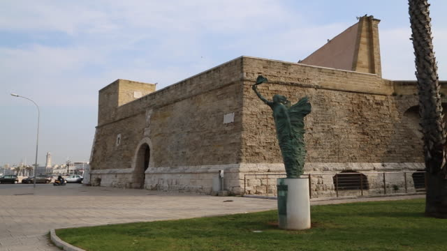 bari, statue in front of a castle in harbour of the city - on the move video stock e b–roll