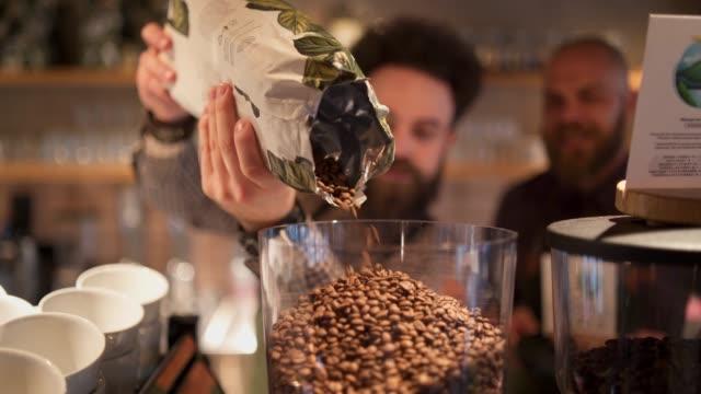 barista aggiunge chicchi di caffè al macinino da caffè - tazza da caffè video stock e b–roll