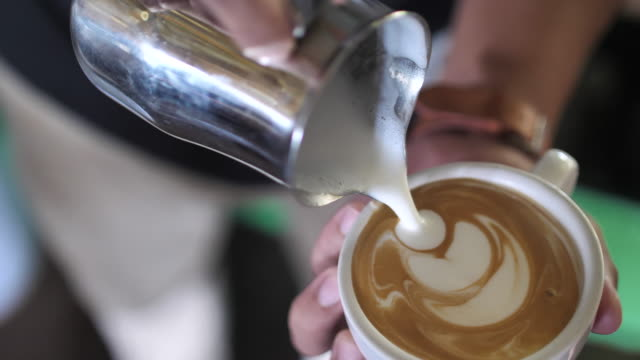 barista adding foamy milk into a cup of coffee for froth art - froth art stock videos and b-roll footage