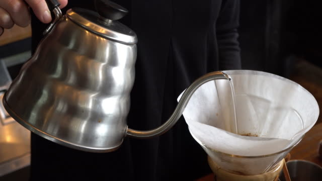 barista black shirt spills hot water prepare filtered coffee from silver teapot to transparent chrome drip maker on white simple weights. everything thick wooden table cafe shop. steam - tea pot stock videos and b-roll footage