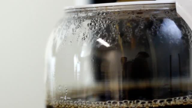 Barista brews coffee in Coffee maker close up