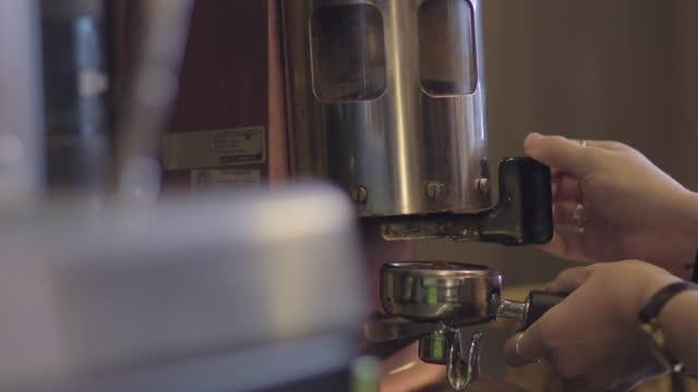 cu. barista cranks coffee grinder back and forth to ground coffee beans. - カフェイン分子点の映像素材/bロール