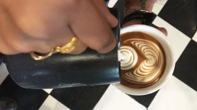 barista create latte art at coffee shop - froth art stock videos and b-roll footage