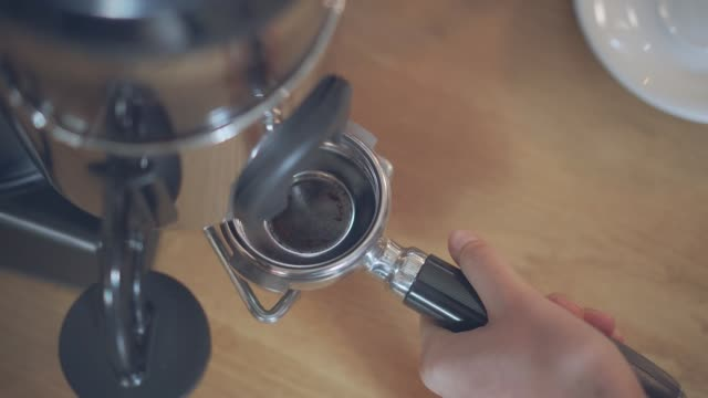 barista grinding coffee beans using coffee machine. - coffee drink stock videos & royalty-free footage