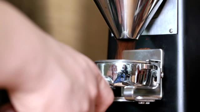 barista mahlt kaffeebohnen zu portafilter. - ausgusstülle stock-videos und b-roll-filmmaterial