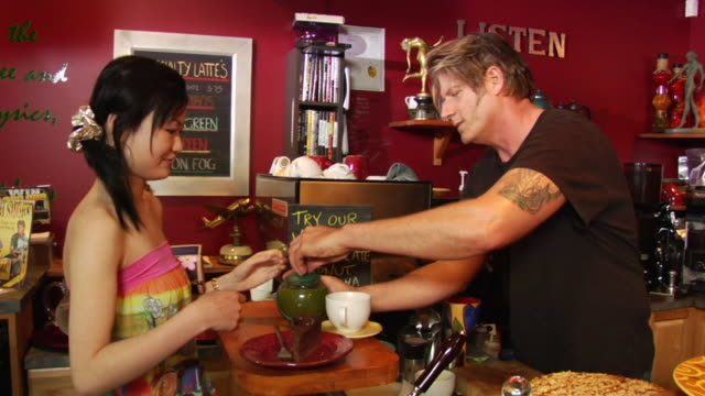 ms barista in coffee shop giving young woman pot of tea and piece of chocolate cake/ vancouver, bc - see other clips from this shoot 1100 stock videos & royalty-free footage