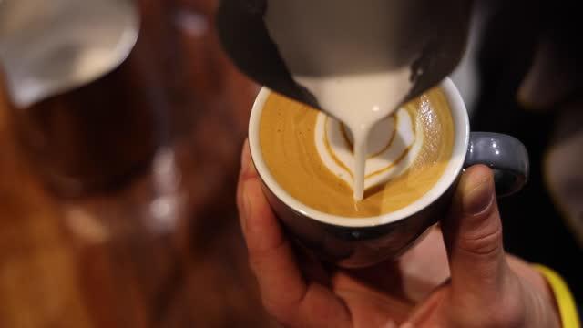 バリスタはコーヒーカップラテアートを作ります - カプチーノ点の映像素材/bロール