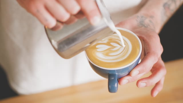 barista making latte art at a cafe - preparation stock videos & royalty-free footage