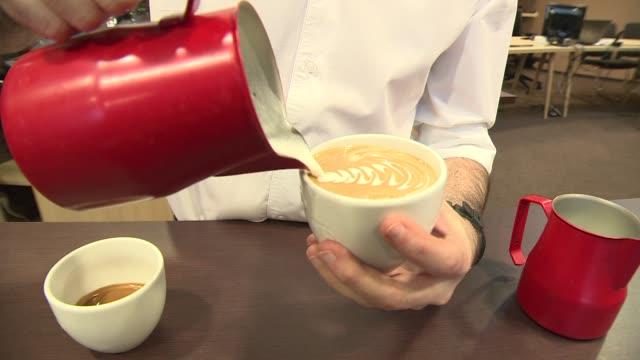 barista making milk pattern on coffee - pitcher jug stock videos & royalty-free footage