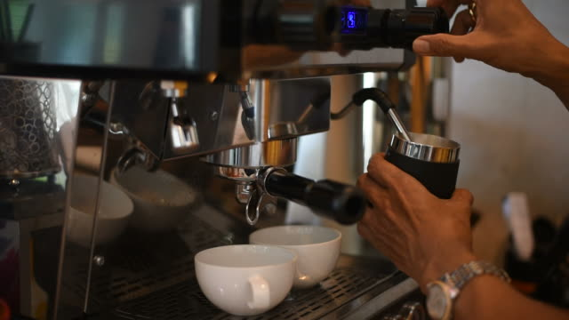 barista making two of coffee latte in coffee bar - cafe macchiato stock videos and b-roll footage