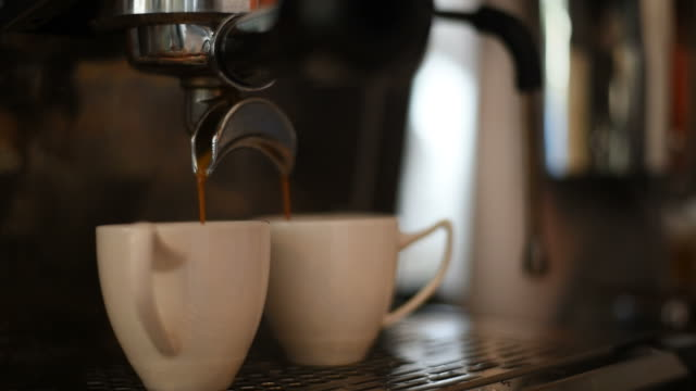 barista making two of espresso in coffee bar. - cafe macchiato stock videos and b-roll footage