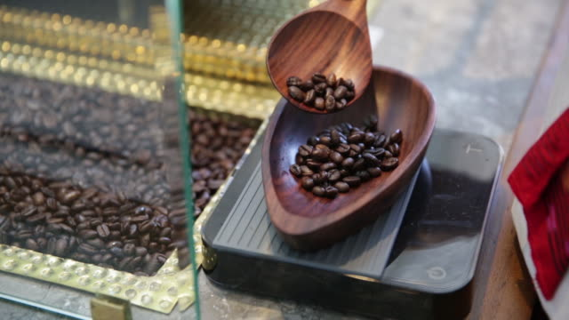 barista pouring coffee beans into wooden bowl at starbucks cafe bali jawa indonesia on sunday january 13 2019 - waage gewichtsmessinstrument stock-videos und b-roll-filmmaterial