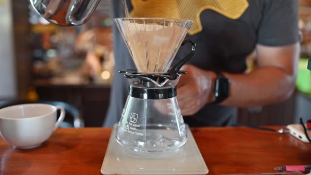barista pouring hot water in paper filter on counter - bricco video stock e b–roll