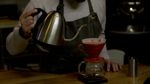Barista pouring water through coffee filter