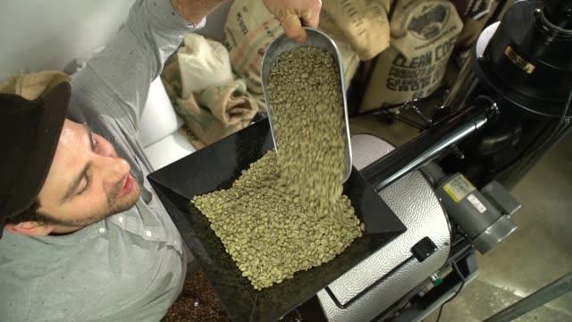 stockvideo's en b-roll-footage met barista roosteren rauwe koffiebonen-slow motion - handen in een kommetje