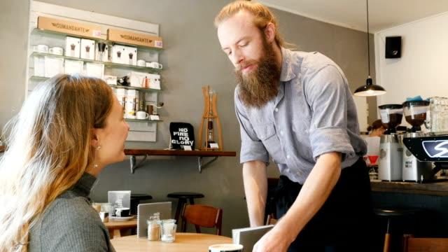 Barista serviert Kaffee zu glücklichen Kunden im Café