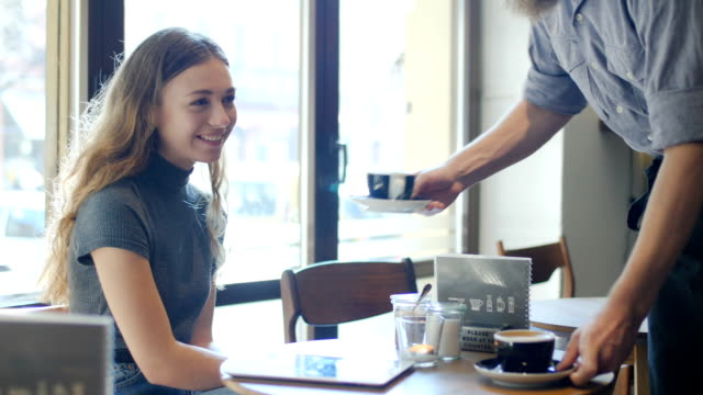 Barista serving coffee to male and female friends