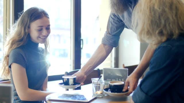 Barista serviert Kaffee, Männliche und weibliche Freunde