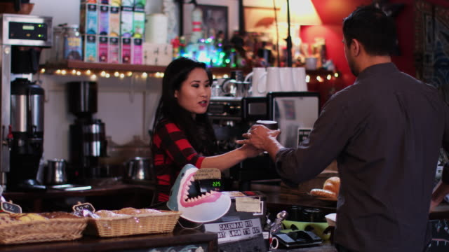 barista serving coffee to man paying with mobile phone - coffee cup stock videos & royalty-free footage