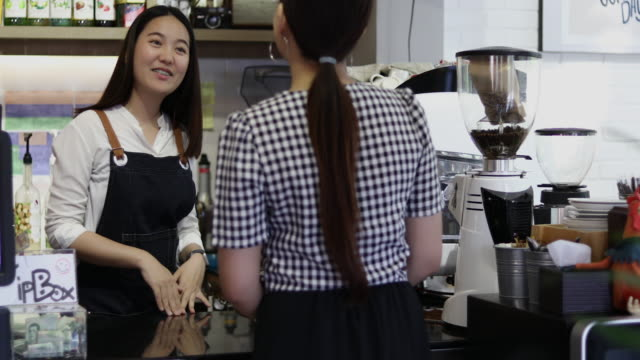 barista serving customer and woman is paying for coffee by credit card in coffee shop - customer focused stock videos & royalty-free footage