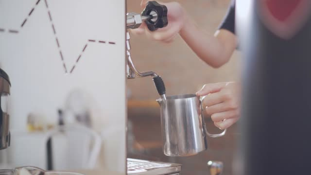 Barista steaming milk at espresso machine in cafe