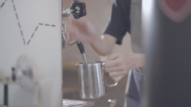 barista steaming milk at espresso machine in cafe - bar drink establishment stock videos and b-roll footage