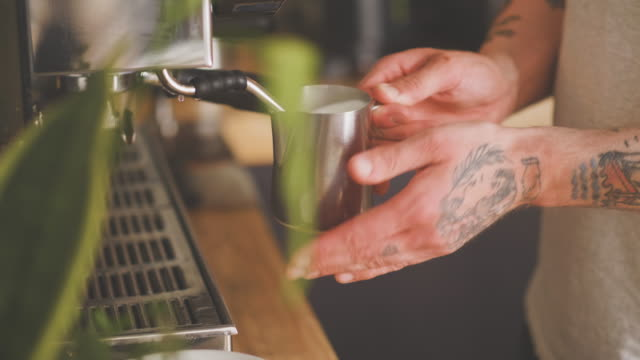 barista steaming milk by the espresso maker - steam stock videos & royalty-free footage