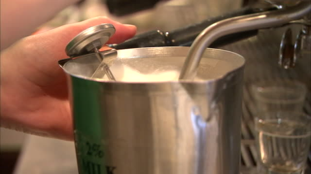 a barista steams milk. - カプチーノ点の映像素材/bロール