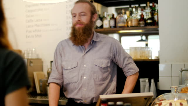 Barista talking with customers in coffee shop
