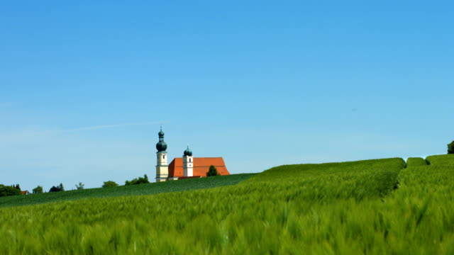 ts barley field in front of the baroque church in aufhausen (bavaria) - baroque stock videos & royalty-free footage