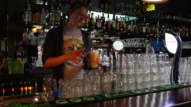 a barmaid pours glasses of draught grolsch beer produced by sabmiller plc in a bar in utrecht netherlands on sunday may 1 2016 - utrecht stock videos and b-roll footage