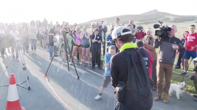 stockvideo's en b-roll-footage met barman kevin carr completes record breaking roundthe worldrun england devon dartmoor ext various of kevin carr cheered by crowd of spectators as he... - menselijke arm