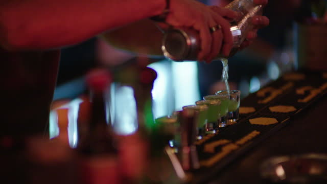 barman mixes drinks and dj plays music in bar - nightlife stock videos & royalty-free footage