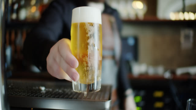 barman offering lager to viewer - pint glass stock videos & royalty-free footage