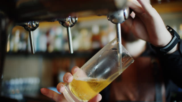 barman pouring a half pint of lager - lager stock videos & royalty-free footage