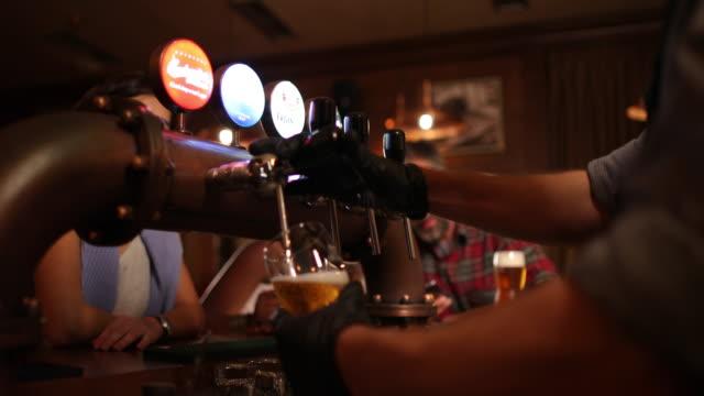 barmann gießt bier in kneipe - pint stock-videos und b-roll-filmmaterial