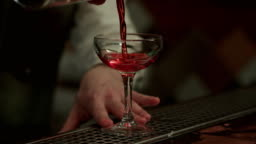 Barman pouring red alcohol preparing cosmopolitan into champagne glass