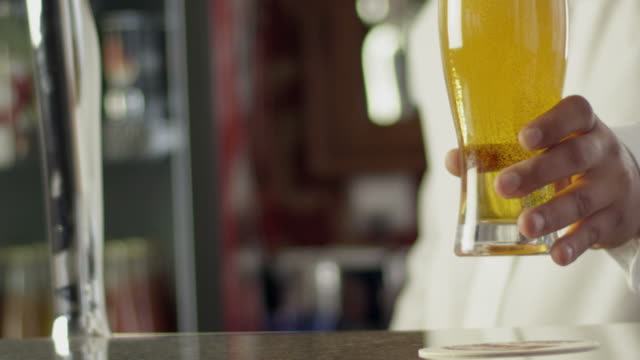 barman pours beer into a glass - bartender stock videos & royalty-free footage