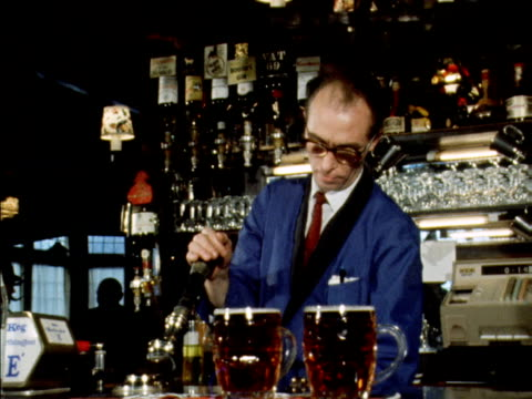 A barman pulls a pint of beer in a pub