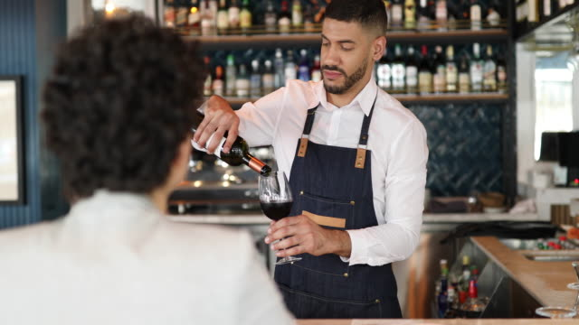 barman serving wine to a woman in pub - part time worker stock videos & royalty-free footage