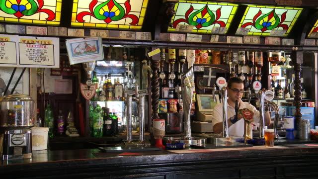 vídeos de stock, filmes e b-roll de ms barman working in angry friar pub / gibraltar - pub
