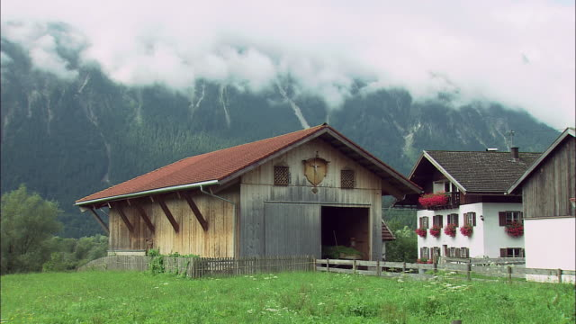 WS Barn in Alpine village, mountains covered with clouds in background, Bavaria, Germany