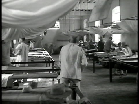 int barracks w/ men bunks two prisoners sitting at small tables by bunks backs to each other eating one prisoner / exile w/ glasses reading paper by... - sick prisoner stock videos & royalty-free footage