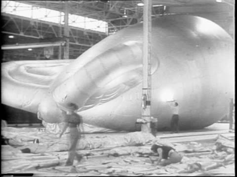 Barrage balloon is laid out and inflated on Akron Firestone Plant factory floor / workers inspect the work by inflating the balloons and looking for...